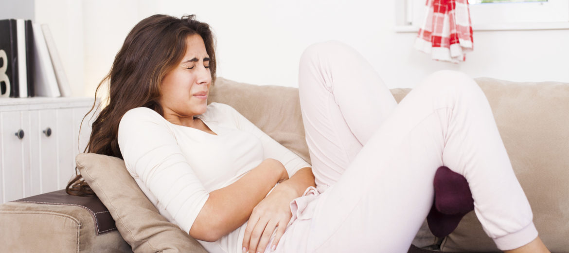 Young woman sitting on the bed with hard stomach pain